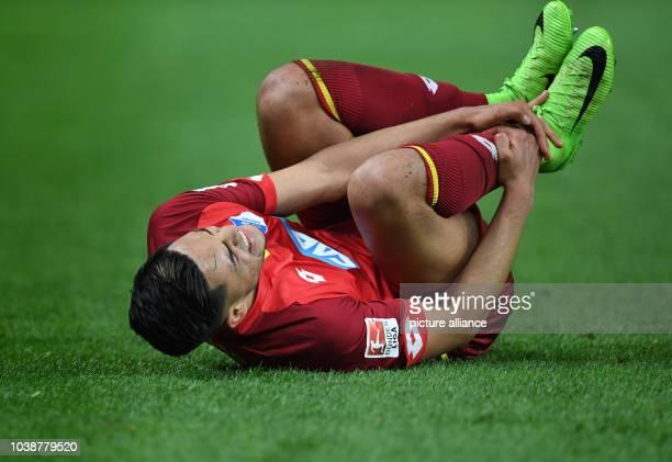 Hoffenheim's Nadiem Amiri lies on the ground after a foul by Berlin's Mittelstaedt who got a red card during a Bundesliga soccer match between Hertha...