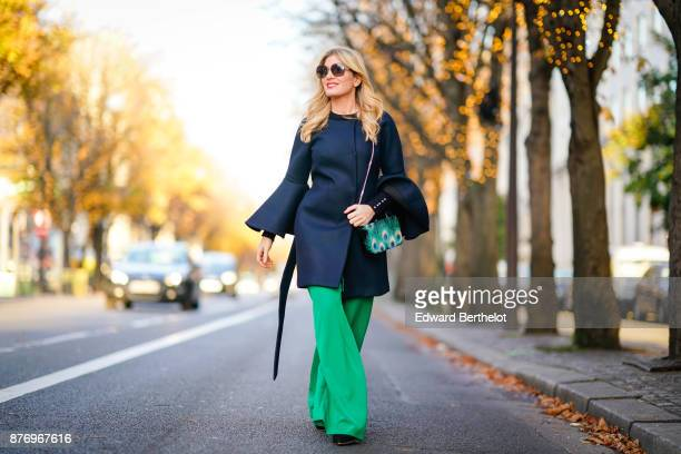 Hofit Golan model and TV host wears a total look by Milly a black top with oversize sleeves sunglasses green flare pants a Gucci bag at avenue...