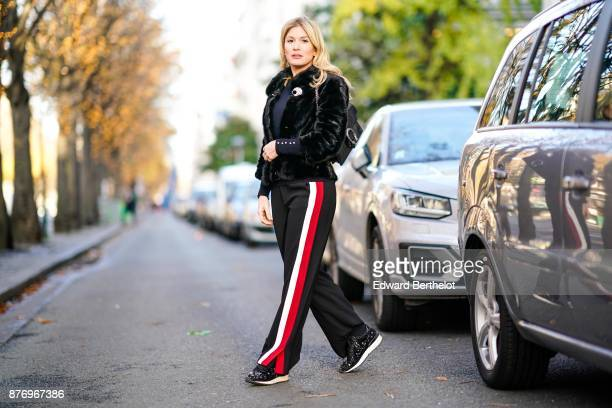 Hofit Golan model and TV host wears Zara sportswear pants with printed stripes a Zara black top a Gucci bag a Gucci black fur coat Casadei shoes at...