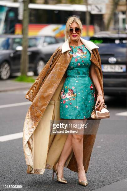 Hofit Golan wears sunglasses, a brown long coat, a green dress with floral embroidery, a bronze color shiny bag, golden pointy shoes, outside Leonard...