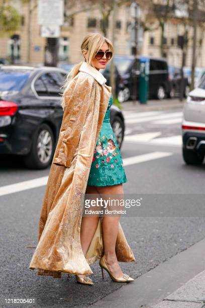 Hofit Golan wears sunglasses a brown long coat a green dress with floral embroidery golden pointy shoes outside Leonard Paris during Paris Fashion...
