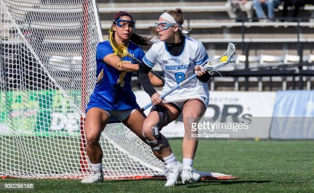 Hofstra Elena Schorr checks Johns Hopkins Miranda Ibello behind the net during a women's college Lacrosse game between the Johns Hopkins Blue Jays...