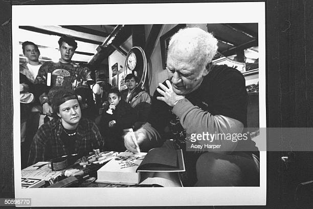Hofstra Univ prof Douglas Brinkley a small group of students looking on as author '60s guru Ken Kesey autographs a copy of a bk for a student at his...