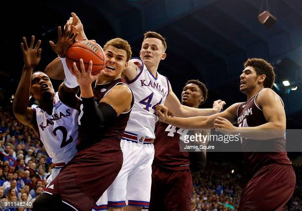 Hogg of the Texas AM Aggies tries to control the ball as Lagerald Vick and Mitch Lightfoot of the Kansas Jayhawks defend during the game at Allen...