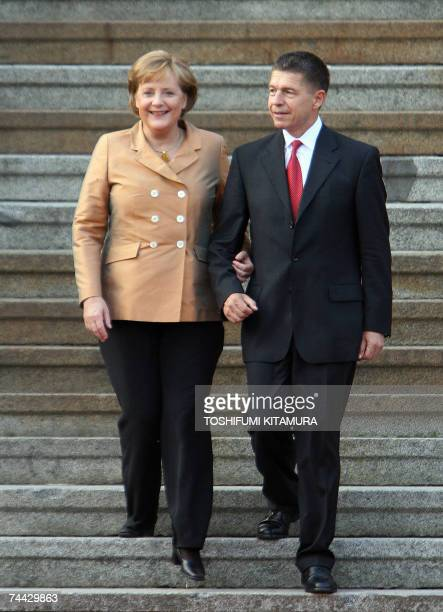 German Chancellor Angela Merkel and her husband Joachim Sauer walk down a stair to welcome G8 summit leaders at the unofficial banquet hosted by...