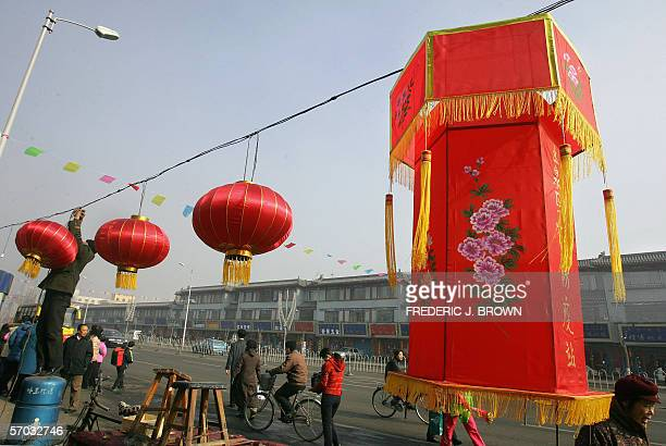 A man hangs red lanterns to decorate a street in Hohhot 11 February 2006 in China's northwest Inner Mongolia Autonomous Region Chinese will celebrate...