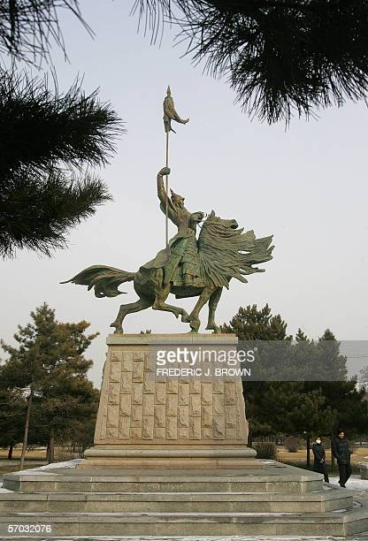 A woman gazes up while walking past a statue of Mongolian hero Genghis Khan on the Inner Mongolia University campus 10 February 2006 in Hohhot...