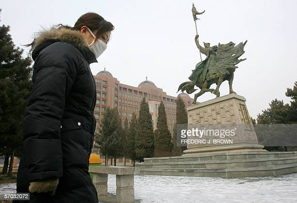 Woman walks past a statue of Mongolian hero Genghis Khan on the Inner Mongolia University campus, 10 February 2006 in Hohhot, capital of China's...