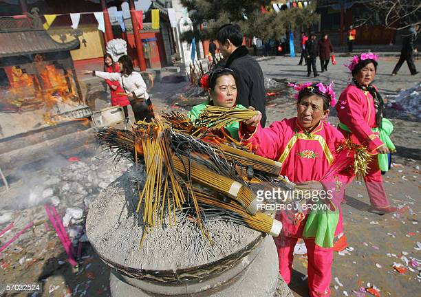 Women in folk dance costume burn incense at Dazhao temple in Hohhot 12 February 2006 where ethnicMongolian monks from the YellowHat sect of Tibetan...