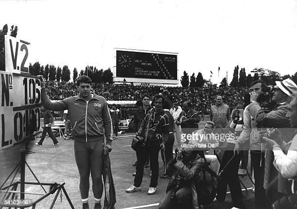 Hohn, Uwe *-Speerwerfer, DDR- Olympischer Tag im Friedrich-Ludwig-Jahn-Sportpark:Weltrekord mit 104,80 Metern: Hohn stehtneben der Anzeigetafel im...