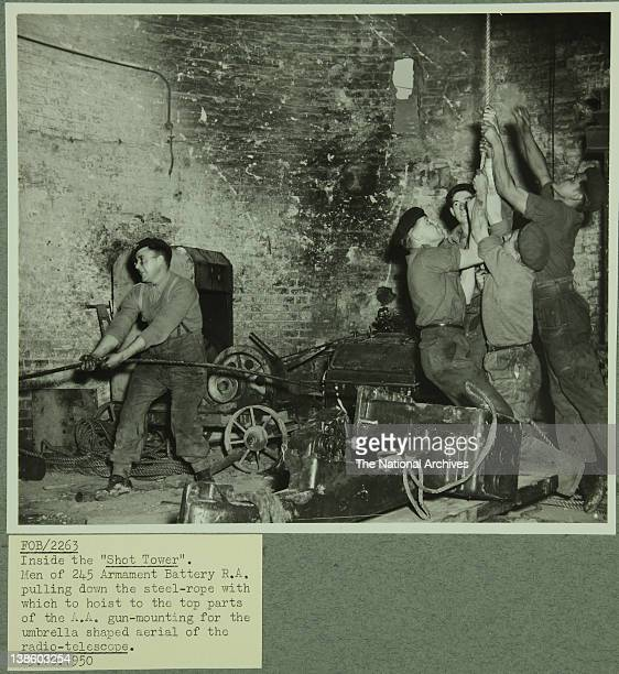 Hoisting the mounting for radio telescope at the Fesitval of Britain Inside the Shot Tower Men of the 245 Armament Battery RA pulling down the...