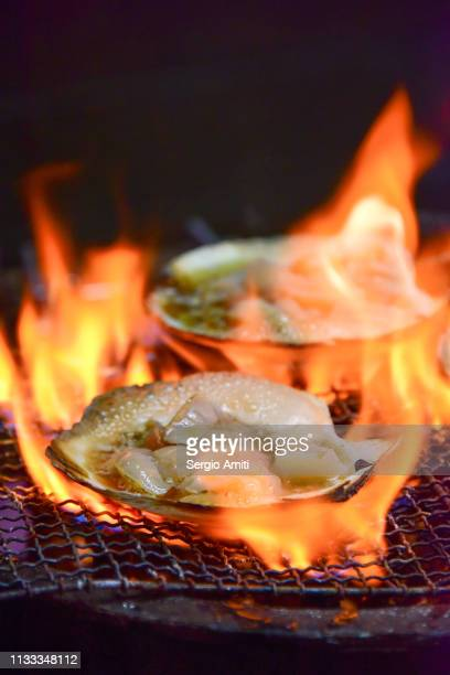 Hokkaido scallops on a grill with flames