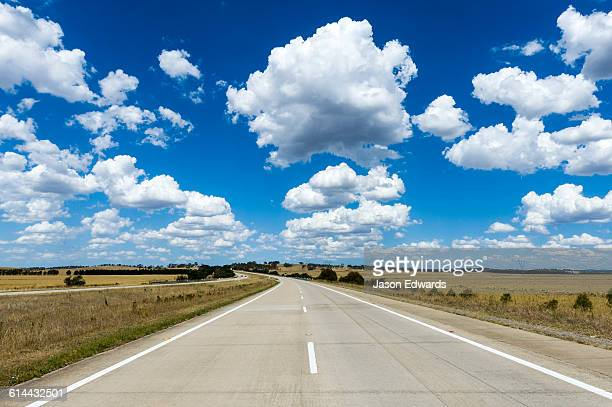 Fluffy white clouds above a highway passing through dry farmland.