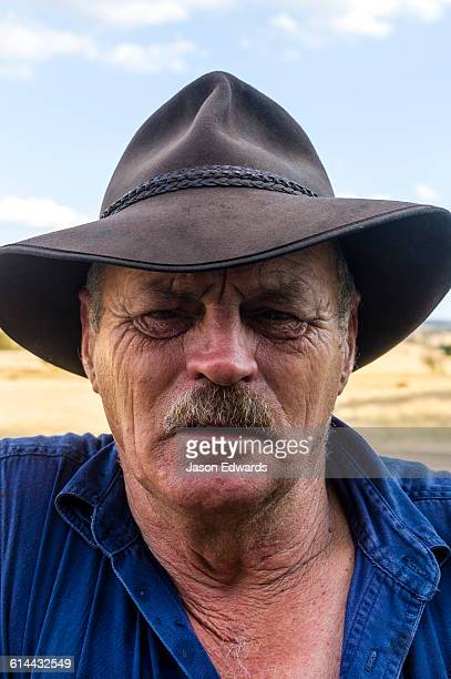 The weathered features of a farmer wearing an akubra slouch hat.