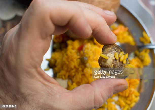 hold clams of the paella with the hand
