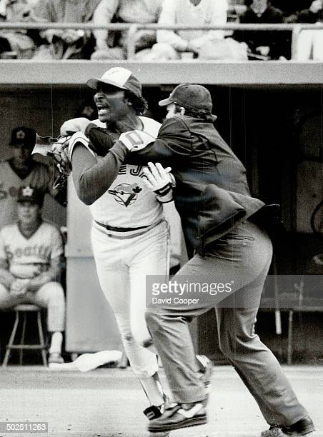 Hold that Blue Jay Umpire Rocky Roe restrains Lloyd Moseby after the Jay batter was hit by a pitch in the fifth inning