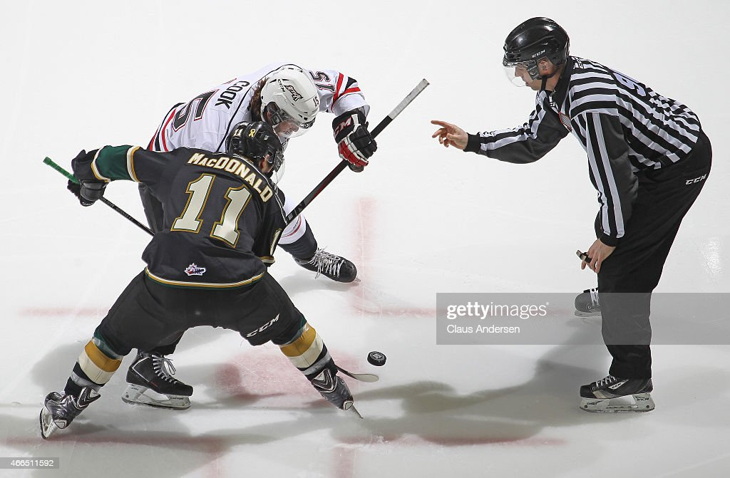 Holden Cook #15 of the Owen Sound Attack takes a faceoff against Owen MacDonald #11 of the London Knights during an OHL game at Budweiser Gardens on March 13, 2015 in London, Ontario, Canada. The Knights defeated the Attack 3-2.