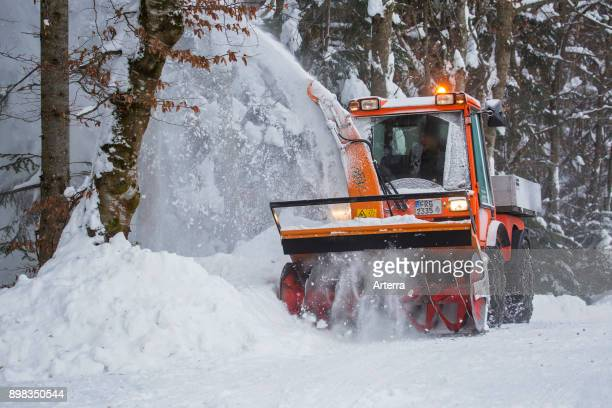 Holder C9700H municipal tractor with snow blower clearing snow from road in forest after heavy snowfall in winter