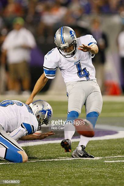 Holder Ryan Donahue holds the ball as kicker Jason Hanson of the Detroit Lions kicks a field goal against the Baltimore Ravens during the first half...