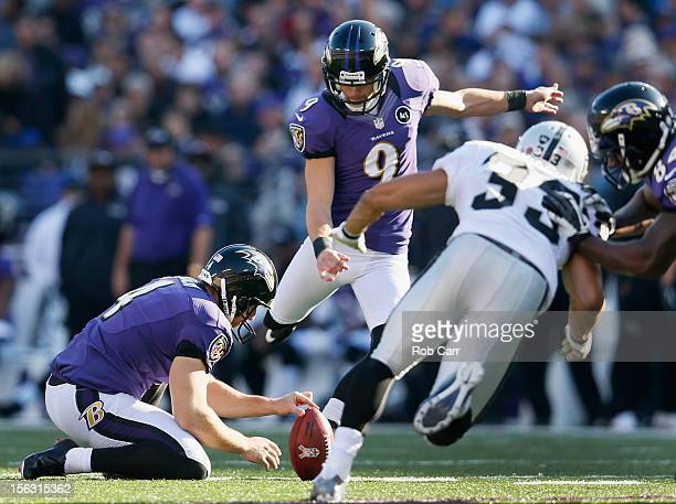 Holder Sam Koch holds the ball as kicker Justin Tucker of the Baltimore Ravens kicks an extra point against the Oakland Raiders at MT Bank Stadium on...
