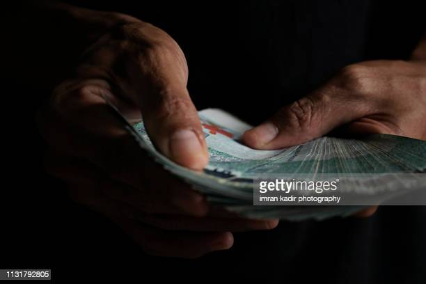 holding 50 ringgit in cropped hand - malaysian ringgit stock photos and pictures