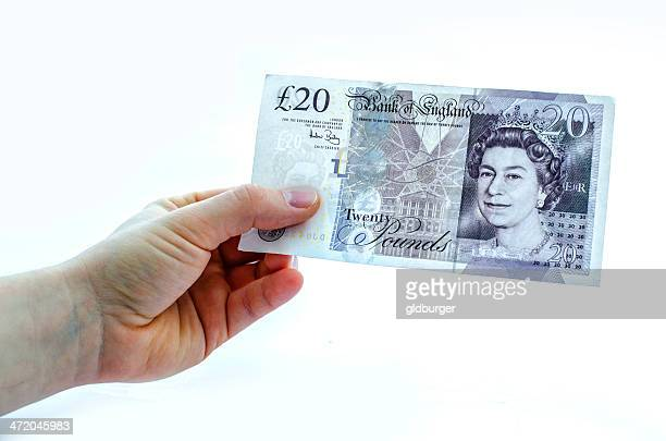 holding a 20 pound note - twenty pound note stock photos and pictures