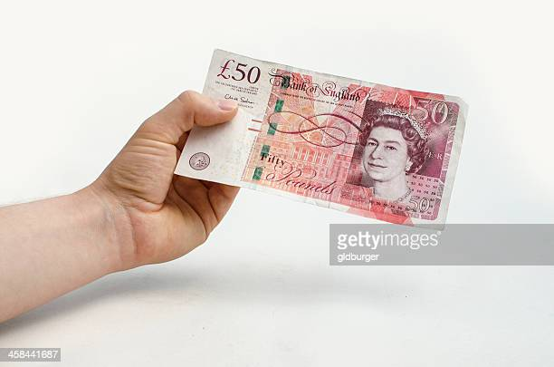Holding a 50 pound note