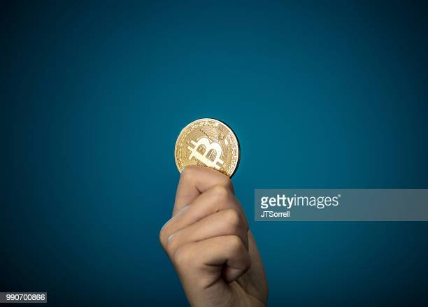 holding a bitcoin - bitcoin stock pictures, royalty-free photos & images