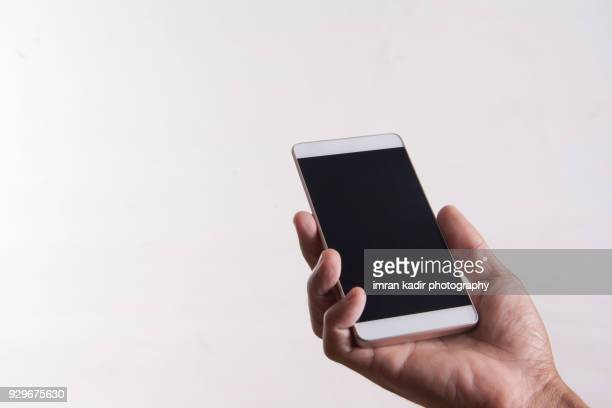 holding a black screen smartphone in white background. - menschliche hand stock-fotos und bilder