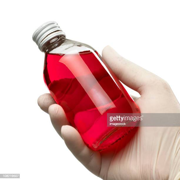 Holding a bottle of cough syrup