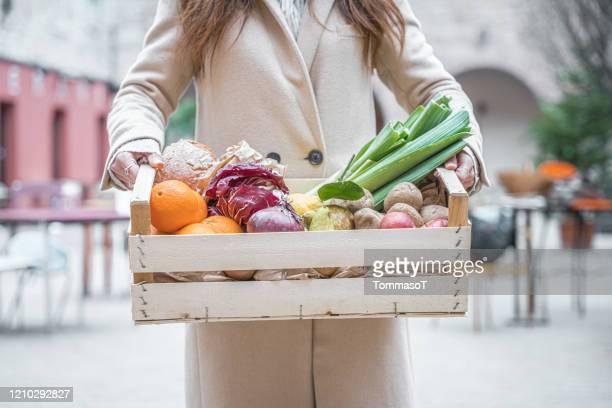 tenant une caisse avec des fruits et légumes - panier photos et images de collection