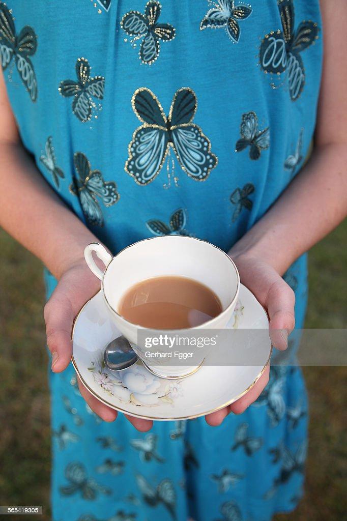 Holding a cup of tea : Foto de stock