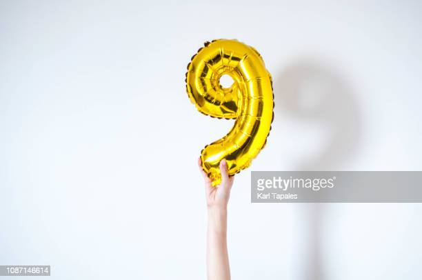 holding a golden-colored inflatable balloon number nine - number 9 stock pictures, royalty-free photos & images