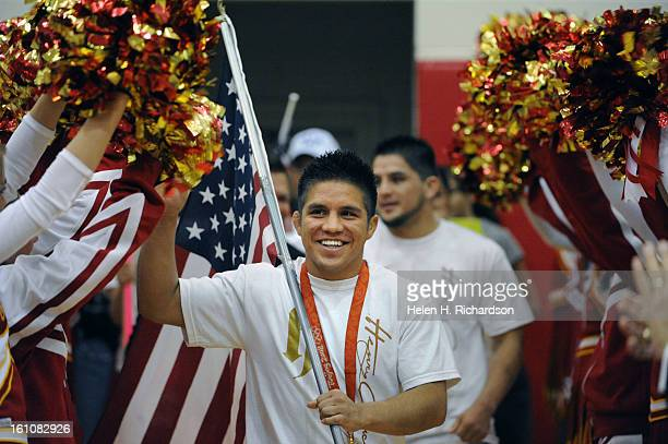 Holding a large American flag Henry Cejudo arrives in the gymnasium to the music from the soundtrack of Rocky and the school's cheerleaders 2006...