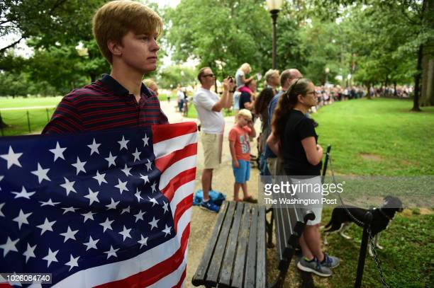 Holding a large US flag Hunter Congdon from New Heaven CT who studies at Georgetown University watches Senator John McCains widow Cindy McCain laying...