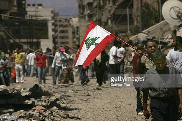 Holding a Lebanese flag, Lebanese people returned to the southern suburbs to check on homes and businesses and to view the damage from Israeli air...