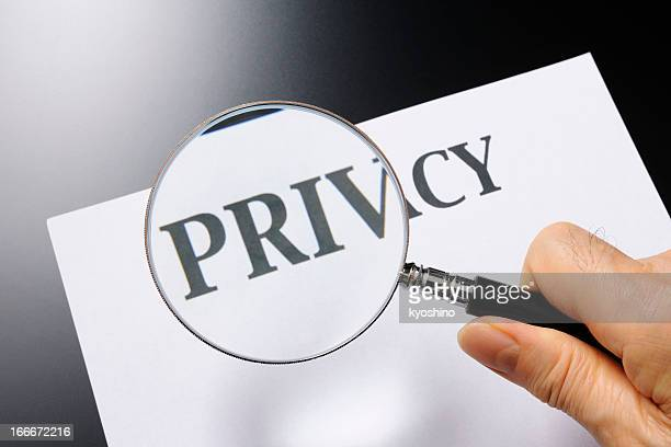 Holding a magnifying glass, looking for privacy
