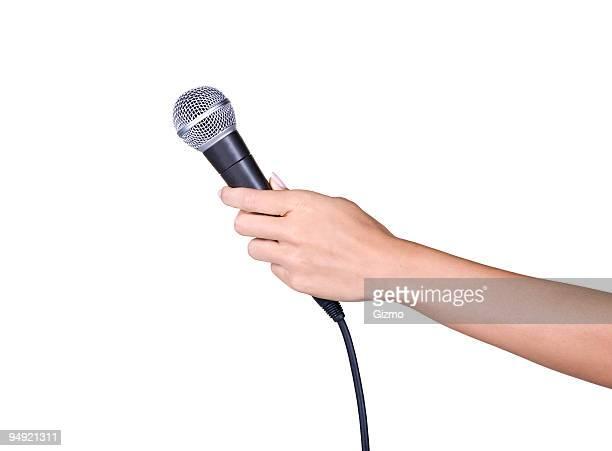 Hält ein Mikrofon