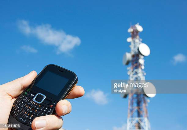 Holding a mobile phone and communication tower