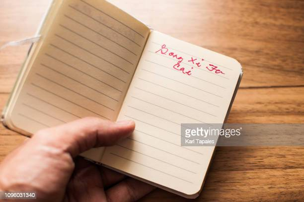 "Holding a notepad with short phrase ""Gong Xi Fa Cai"""