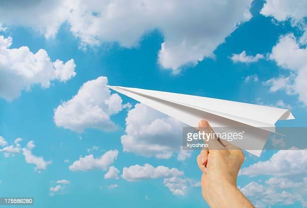 segurando um avião de papel contra céu azul com espaço para texto - aerodinâmico - fotografias e filmes do acervo