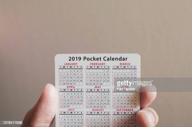 holding a pocket new year calendar - month stock pictures, royalty-free photos & images