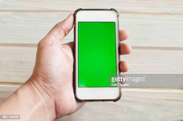 holding a smart phone with green screen - chroma key foto e immagini stock
