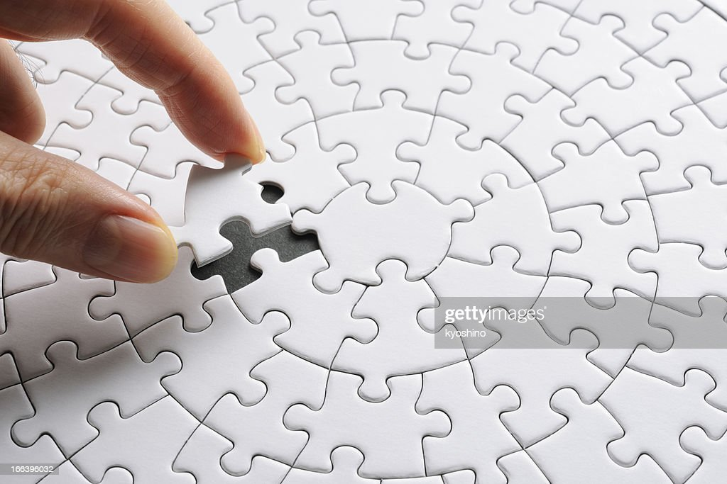 Holding a white blank final piece of the jigsaw : Stock Photo