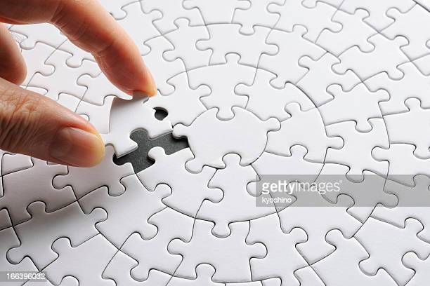 holding a white blank final piece of the jigsaw - finishing stock pictures, royalty-free photos & images