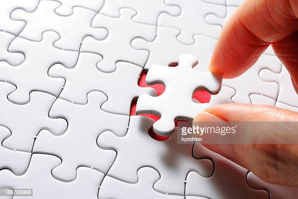 Holding a white blank final piece of the jigsaw
