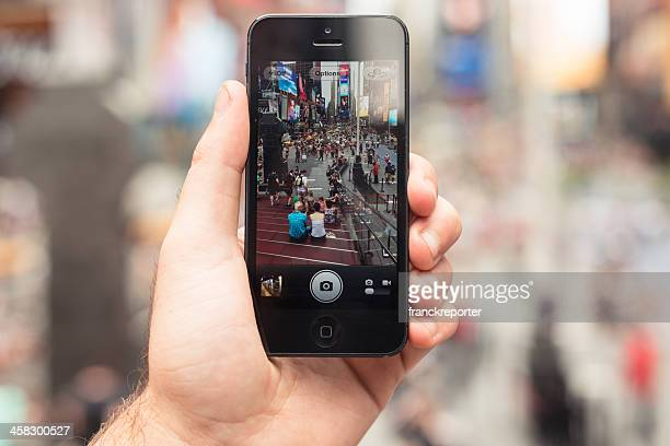 holding an apple iphone 5 on times square - video still stock photos and pictures