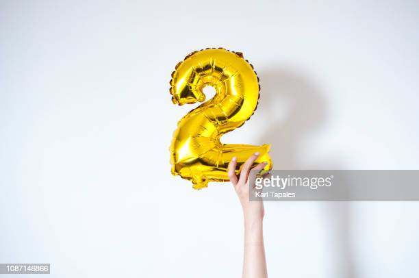 holding an inflatable number 2 balloon - number 2 stock pictures, royalty-free photos & images