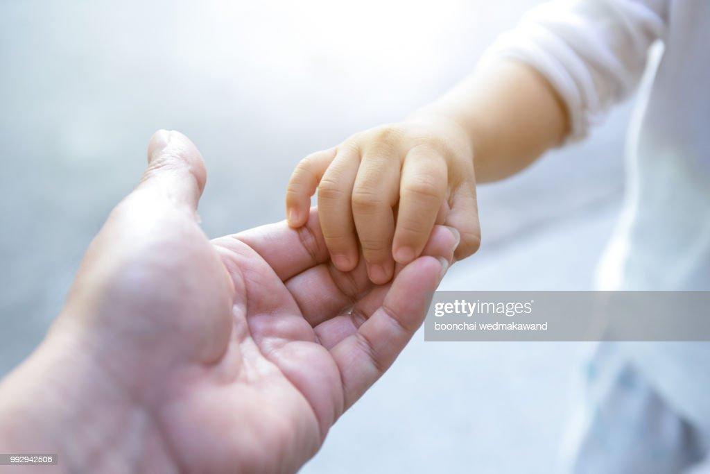 holding baby hand : Stock Photo