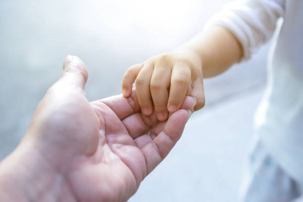 holding baby hand - hand stock pictures, royalty-free photos & images